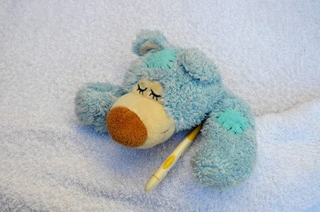 Poor sick teddy in bed with thermometer under arm