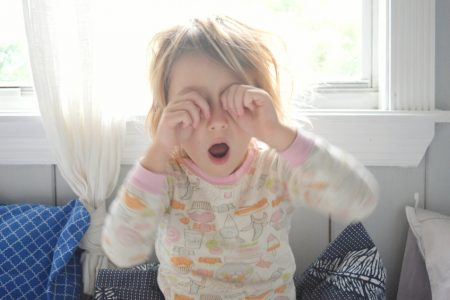 Little girl rubs her eyes and yawns