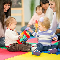 A multi-ethnic group of babies and their mothers playing together with toys in a daycare / preschool setting.