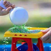 Child is pouring rice out of a scoop into a messy play toy